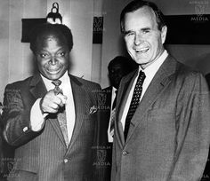 AFRICA, KENYA - Former Vice President George Herbert Walker Bush and Vice President Mwai Kibaki pose for a photograph taken on a state visit as Vice President Mwai Kibaki gestures by pointing towards the camera.