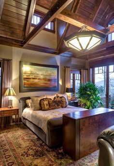 A rustic bedroom with soaring ceilings and rich wood tones. Design by http://www.acmdesignarchitects.com/