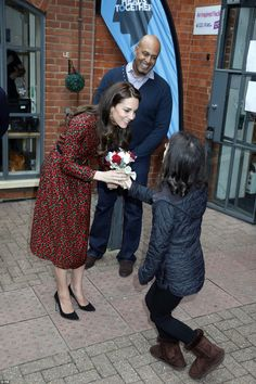 A young woman from The Harrow Club curtsies as she presents The Duchess with a small bunch...
