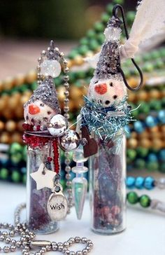 mini men!  Mini snowmen, that is.  Now my little bottle angel  will have a boyfriend.  These little guys can either be hung on the tree or worn as a Christmas adornment around the neck.  Each one has a glass bottle body filled with a transparency image, beads, glass glitter and other Christmasy stuff.  It's cold outside (for most of you!) so these men each wear a scarf made of tinsel, decorated with more beads and tiny charms.  I topped these guys off