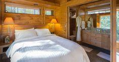 """O quarto e banheiro (à dir.) são integrados na casa de campo """"Escape"""", com 37 m² (internos), situada próximo à cidade de Chetek, Wisconsin (EUA). A cama, os criados-mudos, as arandelas e os armários da bancada da pia são fabricados em madeira, assim como a própria estrutura da construção móvel"""