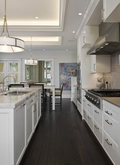 Definitely like the dark floors with the white cabinets. Canvas artwork for the wall. Kitchen Fit for Entertaining (Cultivate.com)