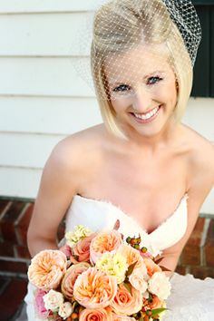 I love everything about this look...the birdcage veil, the peach colored bouquet...loves!