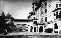 (ca. 1900)* - Exterior view of the Green Hotel in Pasadena. The bridge that extends from the building crosses over Raymond Avenue. Pasadena trolley can be seen travelling on Raymond Avenue.   Water and Power Associates