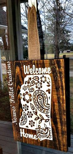 """RECYCLED WOOD PALLETS:  I am officially in Love with this Paisley Design it is our newest creation and it can only be copied, because it is ours! This Welcome Home sign has a hand painted, paisley print that we then stained to give it that creamy color. It comes with a linen burlap ribbon for a hanger. This Mississippi Door Hanger is 16"""" x 11"""" and hangs 24"""". We are selling this piece for $28. Message us if you would like to order one. Item # 898"""