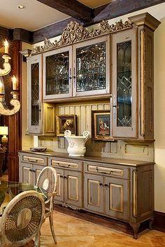 This large china cabinet was designed around the beautiful antique leaded glass windows and the beautiful carved architectural element - Bead board paneling incorporated into the cabinet offers the perfect spot for art