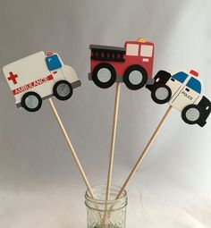 Wooden firetruck, police car and ambulance supported on a wooden dowel can be placed in a bucket or a mason jar with sand or an oasis to create