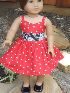 The main dress is a bright cherry red with white polka dot pattern with a black with white flower middle. The dress closes in the back with Velcro.