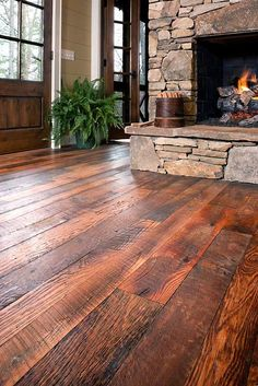 Rustic floor and fire place...love the dark wood floors!