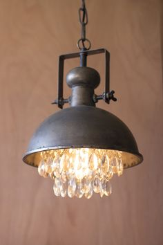 "Industrial meets romantic with this metal pendant lamp. Let the crystals soften the light in any room. 10""d x 13.5""t · UL listed parts · silver metal ceiling cap · six foot black cloth cord · professional hard wiring · Edison 40 watt bulb not included"