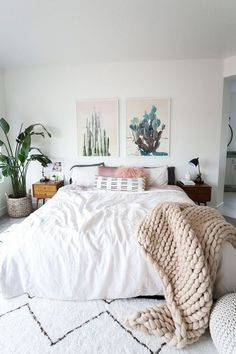 Gorgeous minimalist bohemian bedroom with cactus wall hangs, chunky knit throw and fluffy cushions.