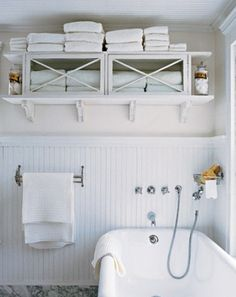 love the panelled wainscoting in this all white bathroom