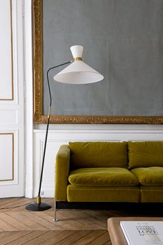 a grand and gilded chalkboard intermingling with dusky olive velvet, a character floor lamp and always elegant chevron floors