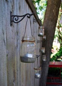 Mason jar tea lights on fence - maybe do this with the solar powered jar lights...