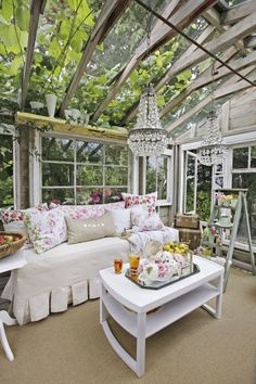 Vintage floral pillows, white-painted furniture, and glass chandeliers give the she shed a truly regal ambiance.