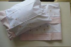 Em Percal 180 fios , Cor Branca , lençóis e fronha com delicado Bordado Ponto Cheio de Flores Mimosas , com detalhe de miolo com miçanga perolada a e Poá rosa bebê . Detalhe bordado em Ponto Palito, com acabamento barrado em Piquet Rosa bebê . Fronha com fecho de sobreposição. <br>Contém 1 lençol de vira + 1 cueiro e 1 fronha . <br>FRONHA - L 28, 5 x C 36 cm <br>CUEIRO - L92 X C 78 cm <br> <br>Bordado à mão