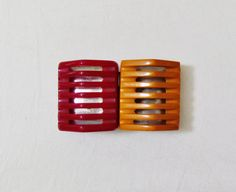 1930s belt buckle made in 2 colors of bakelite, red and caramel, with an interesting design. The pieces are tent-shaped with slits cut
