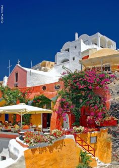 CAFE IN OIA, SANTORINI GREECE| European Travel| The Color Of Beautiful, Blue Skies, Pink,& Yellow Resort | Serafini Amelia
