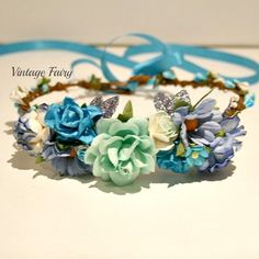 Welcome to Vintage Fairy Gorgeous flower cluster to the front of this gorgeous crown, pretty blue bling leaves make this crown a little more special.lovely blue and white berries circle around a strong and sturdy base Ribbon in the back to tie and extend the size Made to fit newborns up to adults