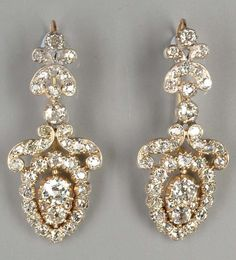A pair of mid Victorian diamond ear pendants. The pear-shaped old brilliant-cut diamond cluster drops, suspended from stylised scroll surmounts and trefoil terminals, to wire hook fittings, mounted in silver and gold, length 3.9cm. #Victorian #antique #earrings