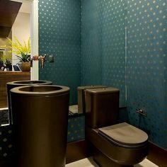 Lavabo com papel de parede azul e peças sanitárias pretas.