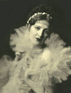 Movie star Billie Dove -  looking into camera and wearing a huge frilly garment