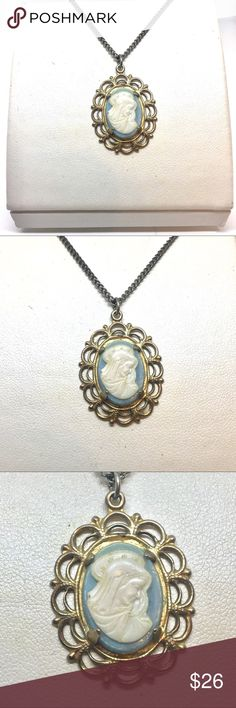 """Religious Saint Blue Cameo Gold Necklace True vintage religious sant blue cameo. Female religious figure with a halo in a veiled scarf. Set in gold tone setting with a double row of scalloped edges in an oval. Chain is 16"""". Pendant is 1"""" by 7/8"""". Not signed or stamped. Vintage Jewelry Necklaces"""