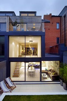 Modern exterior looking through double height glass to interior