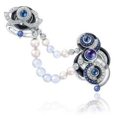 The Chow Tai Fook Le Danse de Temps ring, which matches the necklace, has connecting blue chalcedony beads and pearls to decorate the hand.