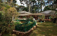 Placas de pínus e telhas translúcidas formam a cobertura ondulada do ateliê da paisagista Mariah Villas Boas, que abriga ainda uma estufa. Em frente, cercas de madeira pintada de verde delimitam o espaço da horta, com temperos e tagetes