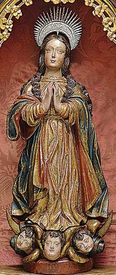 Belíssima imagem de Nossa Senhora da Conceição em madeira com as vestes em belos movimentos drapeados tendo o manto e sobremanto rica pátina em azul esverdeado, vermelho e dourado. O longo cabelo cuidadosamente ondulado cai ao peito e as costas. A imagem, em atitude de prece, pousa sobre três cabeças de querubins e o crescente lunar. Acompanha resplendor em prata. Séc. XVIII. Alt. 89 cm. Base r$25.000,00. Jun16