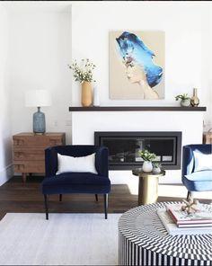 Statement Art Over Fireplace Mantel Painting Woman Navy Velvet Chairs Minimal Decor Living Room Ottoman