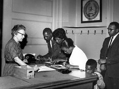 (Left to right) Thomas Chatmon, Marion King, and an unidentified woman register to vote, to the apparent dismay of the office worker, 1962. They are accompanied by young Jonathon King and Slater King (far right).  Albany Movement   New Georgia Encyclopedia