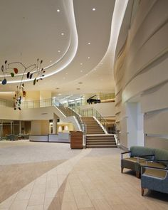 "A grand staircase in the lobby connects the main hospital to the outpatient entry. A ""wave wall"" on the right offers acoustical properties. Kieran Reynolds Photography"