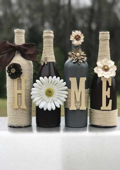 Recycled wine bottles crafted with paint, twine, and letters to spell HOME. These particular bottles are painted in an espresso brown and granite gray. I can customize the colors to fit your needs. Just send me a message with your color preferences. Soda Bottle Crafts, Glass Bottle Crafts, Wine Bottle Art, Diy Bottle, Crafts With Wine Bottles, Bottle Holders, Bottle Labels, Candle Holders, Recycled Wine Bottles