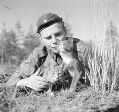 FINISH SOLDIER HAVING A MOMENT WITH 2 CATS