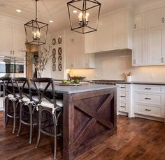 White and navy kitchen features iron and glass cage lanterns over navy center island accented with x trim moldings topped with white and gray stone…