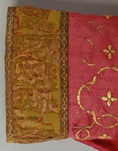 The stockings from the collection of Imperial Regalia at the Kunsthistorisches Museum Wien, Weltliche Schatzkammer, Inventory Number: SK_WS_XIII_12. These are made of red silk, with gold embroidery and tapestry-woven green silk cuffs.