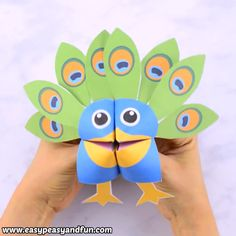 Amazing printable peacock cootie catcher. Learn how to make a peacock fortune teller with our printable template. This is a cool origami for kids to make, easy peasy! This craft for kids can be printed in color or as a black and white template to color. Super fun paper toy and a puppet for kids to play with.