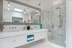 Elegáns fürdőszoba - szürke keretben hatalmas tükör, fehér bútor, épített zuhanyfülke ülőkével, tiszta üvegfallal és ajtóval, pultba süllyesztett mosdó