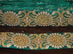 Emeral Green color handmade fabric trim. It is embellished with gold color braid work.This border has been made using raw silk , jari gota and sequins.  This stunning lace can be used for...