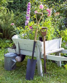 Wheelbarrow filled with flowers and surrounded by garden tools. Bucket Gardening, Container Gardening, Site Art, Metal Watering Can, Watering Cans, Wheelbarrow Planter, Plants For Hanging Baskets, Pot Jardin, Flower Cart