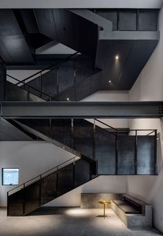 Shanghai studio Neri&Hu has converted a former missile factory in Beijing to create a car repair garage and offices with an industrial-style metal staircase, mesh cages and painted brickwork.