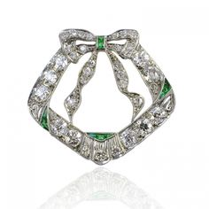 Art Deco Diamond Brooch, Circa 1925 - The modifed chevron design surmounted with a streaming bow, decorated throughout with simulated emeralds and lavishly set with diamonds totaling approximately 2 carats, approximately 1 1/4 inched wide and 1 1/8 inches long. Platinum*