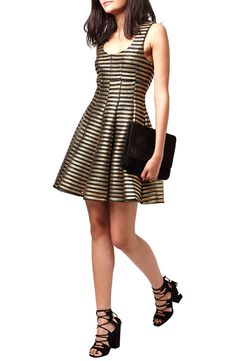 Creating the perfect New Year's Eve outfit with this black and gold striped skater dress that pairs easily with black heels and a clutch.