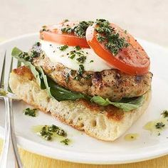 Pesto Chicken Burgers - Fresh mozzarella cheese tops these grilled chicken burgers. They're served on a slice of ciabatta bread that's been topped with fresh basil leaves.