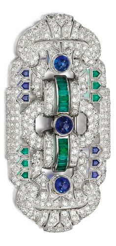 An Art Deco sapphire, emerald and diamond brooch/pendant, 1930s. Of geometric pierced panel design, set with single- and circular-cut diamonds, cabochon, baguette and shield-shaped sapphires and emeralds, hinged pendant bail. #ArtDeco
