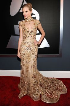 For all those who criticize Taylor Swift for not trying new red carpet looks, the country songstress stepped out of her girly-girl comfort zone in this glitzy Zuhair Murad number. She simply looked like royalty in her gold-emblazoned gown. The high-neck design with dragon embroidery was clearly influenced by the East and Taylor played up the cultural homage with a sleek high bun.  Brand: Zuhair Murad