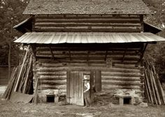 """July 1939. Person County, North Carolina. A tobacco curing barn ready for """"putting in,"""" with fuel stacked on either side. The sticks are fed in through the small openings at the base. Piece of sheet iron on the left is used to cover the opening of the furnace when starting the fire. Medium-format nitrate negative by Dorothea Lange for the Farm Security Administration."""