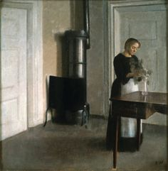 Interior of Woman Placing Branches in a Vase on Table   -   Vilhelm Hammershoi    1900   Danish  1864-1916